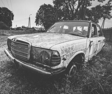grayscale photo of car near trees