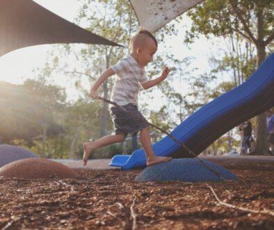 boy stepping on rocks in playground during daytime